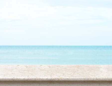holiday display: White marble table top with blurred sea and blue sky at background, Mock up template for display or montage of your product, Summer holiday concept. Stock Photo