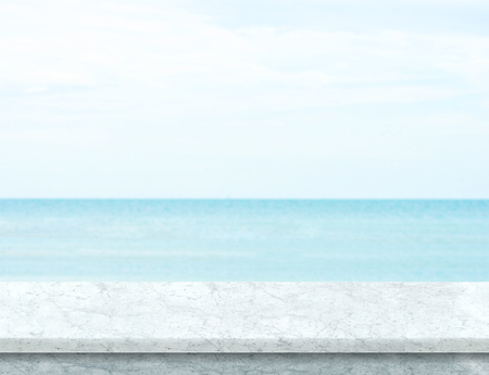 White marble table top with blurred sea and blue sky at background, Mock up template for display or montage of your product, Summer holiday concept. Archivio Fotografico