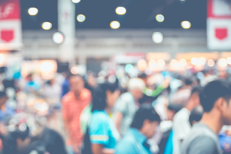 Blurred background: crowd of people in expo fair with bokeh light ,Vintage filtered.
