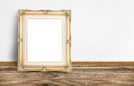 frame wall: Blank golden vintage picture frame leaning at rustic wooden floor and white wall, Template mock up for adding your design and content.