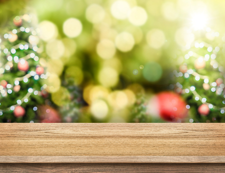christmas light: Brown Wood table top with abstract blur christmas tree background with bokeh light,Holiday backdrop,Mock up for display or montage of product.