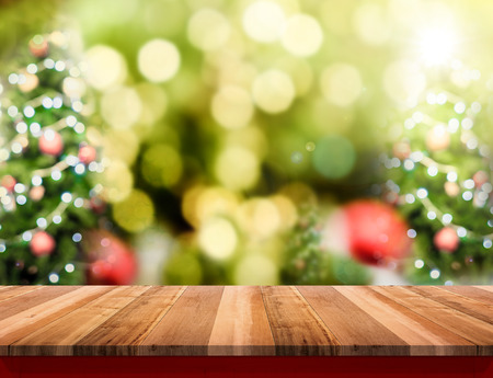 Brown Wood table top with abstract blur christmas tree background with bokeh light,Holiday backdrop,Mock up for display or montage of product.