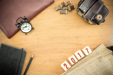 space for type: Red 2017 New year number on Wooden Table top with clock,type box,notebook,leather bag and pencil, Holiday concept,Leave space for adding text.