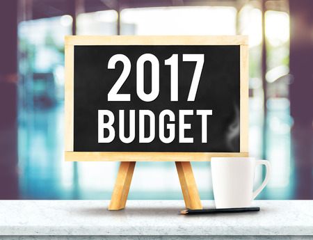 2017 budget on blackboard with easel on black marble table with coffee cup and pencil on blurred building hall way background,New year business plan concept.
