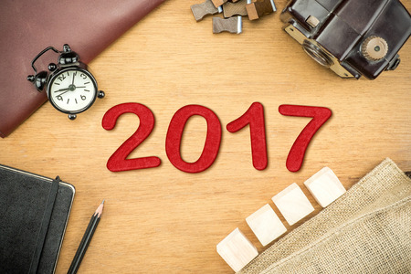top of the year: Red 2017 New year number on Wooden Table top with clock,type box,notebook,leather bag and pencil, Holiday concept.