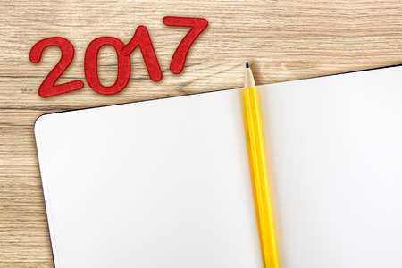 top of the year: Top view of 2017 new year red number with blank open notebook and yellow pencil on wooden table top,Mock up for adding your content or design. Stock Photo