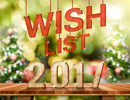 Wish list 2017 number on Brown Wood table top with abstract blur christmas tree background with bokeh light,Holiday Greeting card.