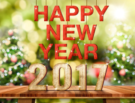 top of the year: Happy New Year 2017 number on Brown Wood table top with abstract blur christmas tree background with bokeh light,Holiday Greeting card.