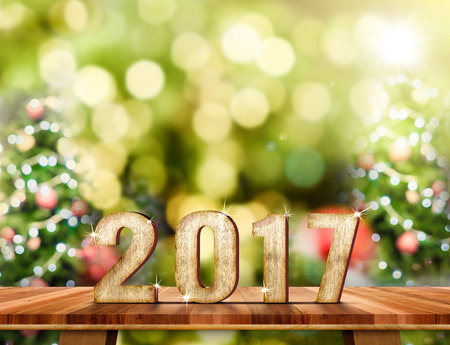 New Year 2017 number on Brown Wood table top with abstract blur christmas tree background with bokeh light,Holiday Greeting card