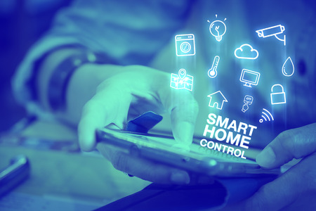 Close up woman using mobile phone with Smart home control word and icon features, Digital lifestyle concept,Duotone color filtered. Stockfoto