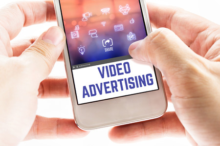users video: Close up Two hand holding mobile phone with Video advertising word and icons, Digital Marketing concept.