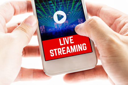 Close up Two hand holding mobile phone with live streaming word and concert event, Digital Marketing concept. Standard-Bild