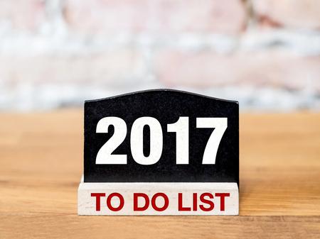 hacer: Año Nuevo 2017 para hacer la lista en la Muestra de la pizarra en la mesa de madera en la pared de ladrillo