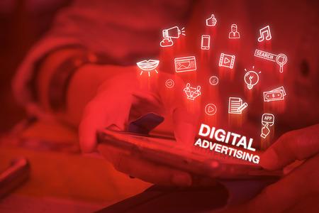 Chiuda sulla donna con il cellulare con la parola pubblicità digitale e le caratteristiche icone, concetto di stile di vita digitale, colore due tonalità filtrata.