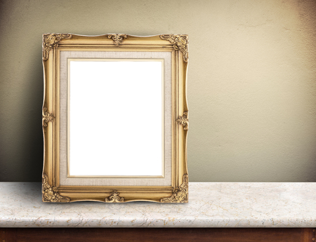 photo frame: Blank Gold victorian picture frame on marble table at yellow concrete wall,Template mock up for adding your design and leave space beside frame for adding more text Stock Photo