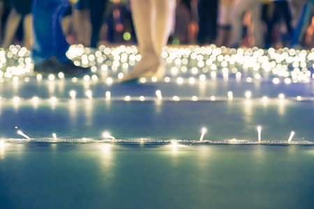 DAnce background: Blurred background,low angle view of people walk at night event fair with bokeh light. Stock Photo