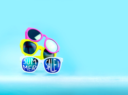 adding: Stack of  Sunglasses and summer sale word in light blue studio,Summer Time concept,Leave space for adding your content or text.
