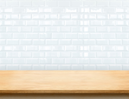 Empty beige wood table top with glossy ceramic white tile wall,Mock up for display or montage of product. Фото со стока