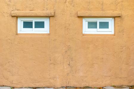 stucco texture: Stucco orange wall with white window texture background. Stock Photo