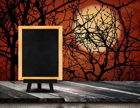 grunge tree: Blackboard with easel on grunge plank wooden table top at spooky tree and full moon with dead tree,Halloween holiday card,Template mock up for display or montage of product.