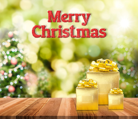 christmas lights display: Merry Christmas (3d rendering) red glitter word and golden present on brown wood table with christmas tree blurred bokeh light,Holiday greeting card.