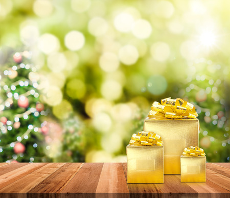 christmas lights background: Golden presents on wood plank table top with christmas tree blurred bokeh light, Mock up for adding your content.