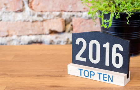 top ten: Top ten topic of 2016 year on blackboard sign and green plant on wood table at brick wall