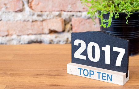 Top ten topic of 2017 year on blackboard sign and green plant on wood table at brick wall