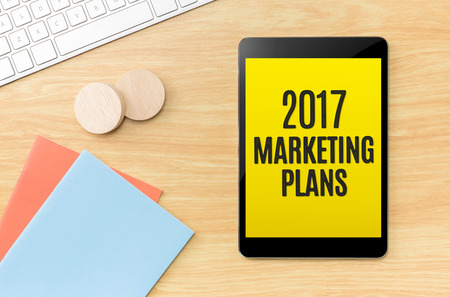 marketing concept: Top view of 2017 marketing plans on screen tablet with blue notebook and keyboard on wooden beige color table top,new year planing.