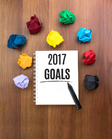self discovery: Top view of 2017 goals on open notebook with black pencil with colorful crumpled paper ball on dark brown table top,Leave space under book to add you text