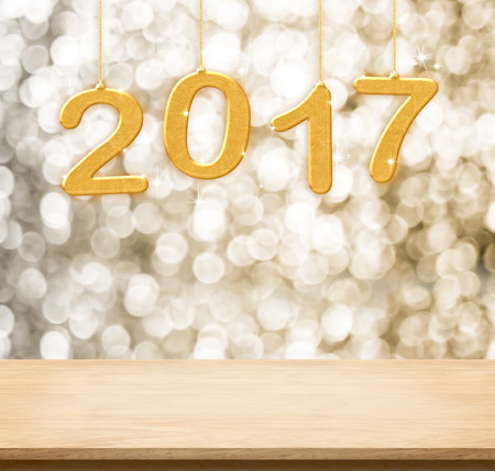christmas lights display: 2017 new year hanging over plain wood table top with gold sparkling bokeh wall,Holiday concept,leave space for adding your content.