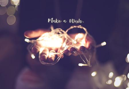 ビンテージ フィルター、休日引用クリスマス シーズンに含まれる光のボケ味を持つ手の上の希望単語を作る。