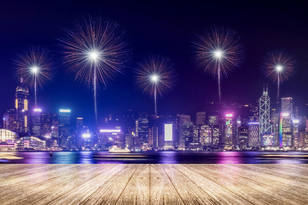 Empty wood plank floor with fireworks over cityscape at night background,Mock up template for display or montage of product for social media advertising,Celebration season.