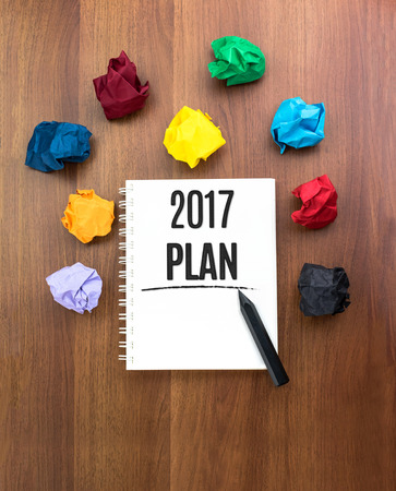 self discovery: Top view of 2017 plan on open notebook with black pencil with colorful crumpled paper ball on dark brown table top,Leave space under book to add you text