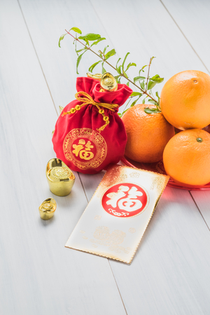 Chinese New year,golden envelope packet (ang pow) and red felt fabric bag with gold ingots and oranges and flower on white wood table top,Chinese Language mean Happiness Stock Photo