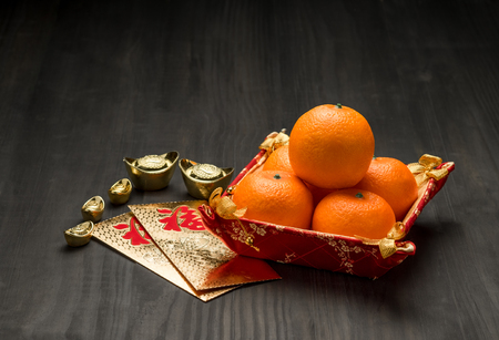 Chinese New year,golden envelope packet (ang pow) with gold ingots and oranges on brown wood table top,Chinese Language mean Happiness. Stock Photo
