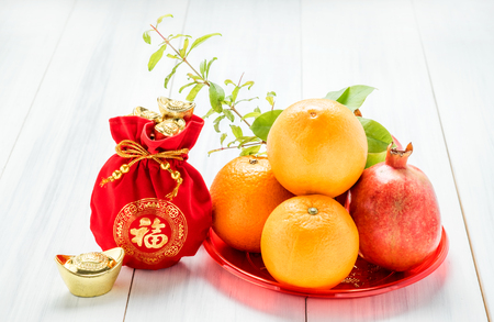 Chinese New year,red felt fabric bag with gold ingots and oranges and flower on white wood table top,Chinese Language mean Happiness