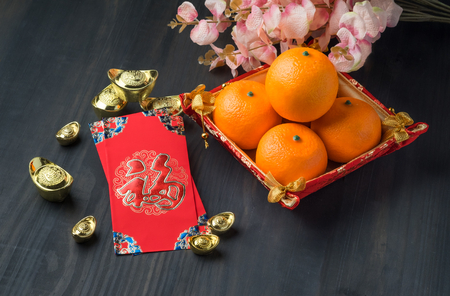 Chinese New year,Red envelope packet (ang pow) with gold ingots and oranges and flower on brown wood table top,Chinese Language mean Happiness Stock Photo