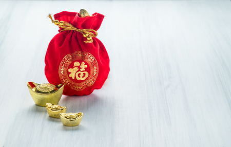 Chinese new year decoration,red fabric packet or ang pow with chinese style pattern and golden ingots on wood table top, Chinese Language mean Happiness,Leave space for add text. Stock Photo