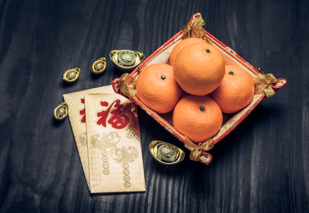 top of the year: Chinese New year,golden envelope packet (ang pow) with gold ingots and oranges on brown wood table top,Chinese Language mean Happiness