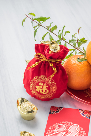 Chinese New year,red envelope packet (ang pow) and red felt fabric bag with gold ingots and oranges and flower on white wood table top,Chinese Language mean Happiness