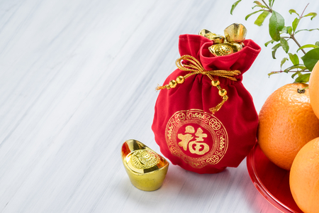 Chinese New year, close up red felt fabric bag with gold ingots and oranges on white wood table top,Chinese Language mean Happiness