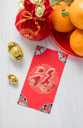 Chinese New year,red envelope packet (ang pow) and felt fabric bag with gold ingots and oranges on white wood table top,Chinese Language on envelop mean Happiness and on ingot mean Wealthy.
