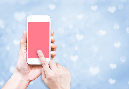 hand phone: Hand holding mobile phone with finger touch on pink screen on blur pastel  blue heart bokeh light background, Valentine greeting card,Mock up template for adding text or design for online media. Stock Photo