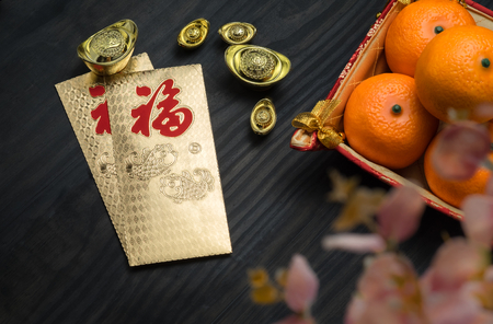 top of the year: Chinese New year,golden envelope packet (ang pow) with ingots and oranges and flower on brown wood table top,Chinese Language on envelop mean Happiness and on ingot mean Wealthy. Stock Photo