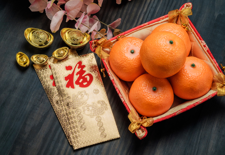 Chinese New year,golden envelope packet (ang pow) with gold ingots and oranges and flower on brown wood table top,Chinese Language mean Happiness Standard-Bild
