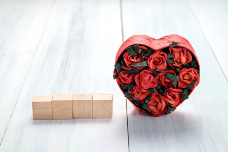 Heart shape box with red roses inside and blak cube on white wood table top ,Love Valentines concept,Mock up for display of text on cube.