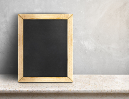 Blank blackboard on beige marble table at grey concrete wall,Template mock up for adding your design and leave space beside frame for adding more text..