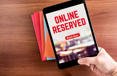 Top view of hand holding tablet with online reserved word with blur restaurant over color notebook on wooden table top,Digital business concept Banco de Imagens