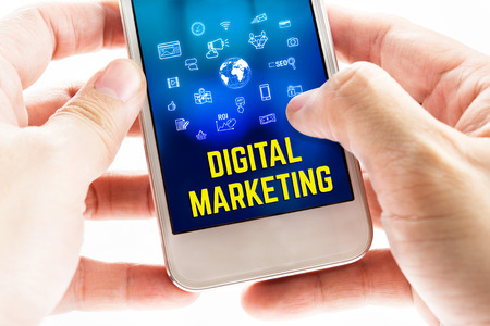 mobile marketing: Close up Two hand holding mobile phone with Digital marketing word and icons, Digital Marketing concept.